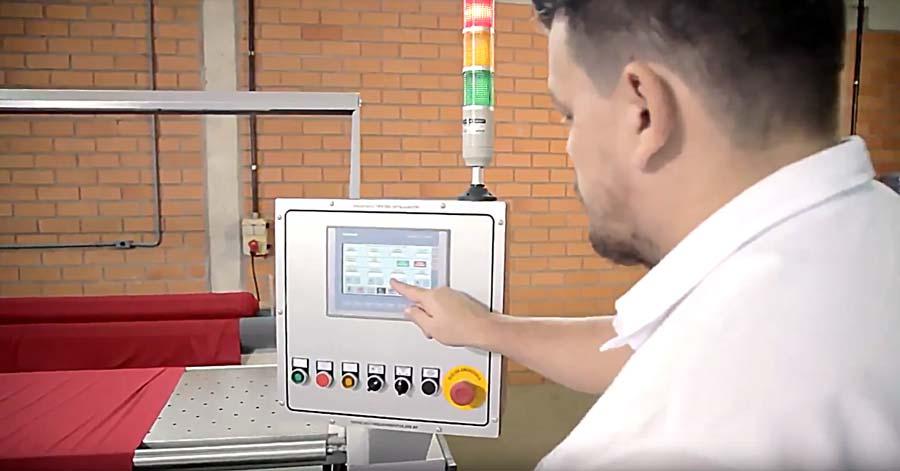 Homem corrigindo problemas em um painel eletrônico em uma fábrica de confecção.