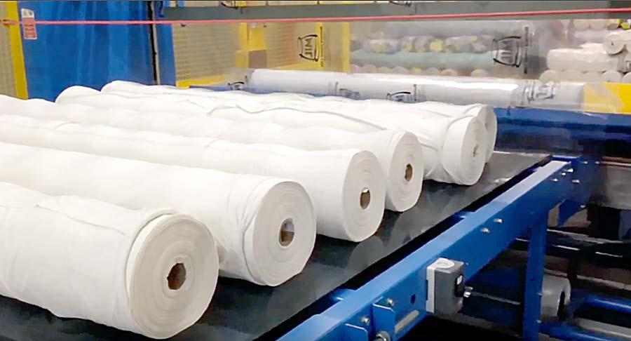 Embaladeira da DELTA, com rolos de tecidos em uma fábrica de confecção.