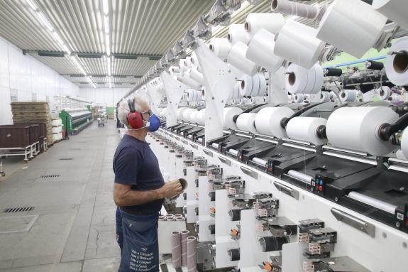 Operário trabalhando em uma indústria de produção têxtil.
