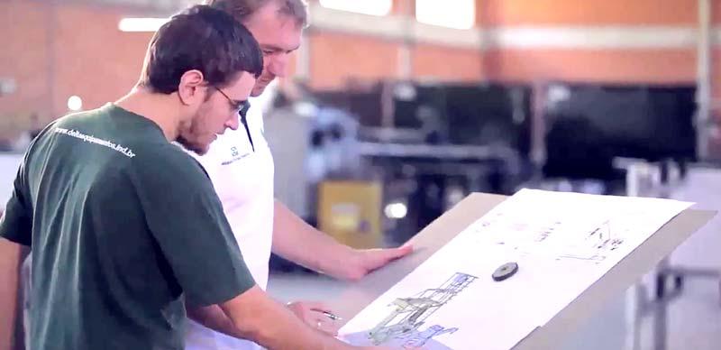 Dois homens trabalhando em um planejamento de manutenção industrial têxtil.