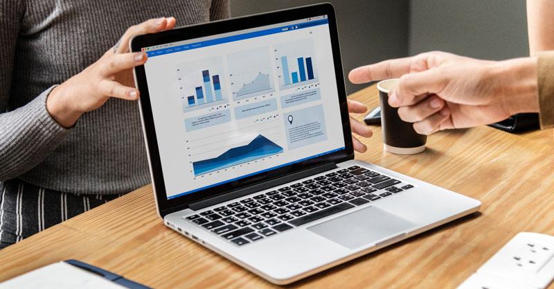Dados sobre o controle de qualidade têxtil sendo apontado na tela de um computador.