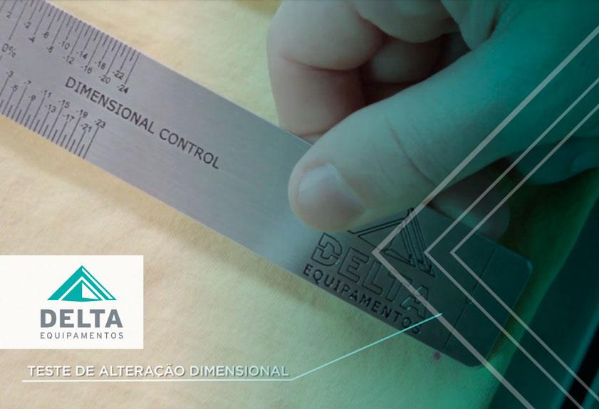 A mão de uma pessoa realizando o teste das marcações na malha com uma régua, a cena é parte do controle de qualidade na confecção realizado com a lavadora de amostras da Delta.