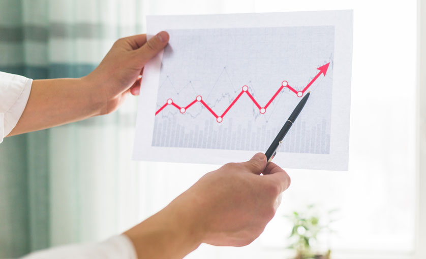 Homem segurando um gráfico de crescimento da produtividade têxtil em uma confecção.