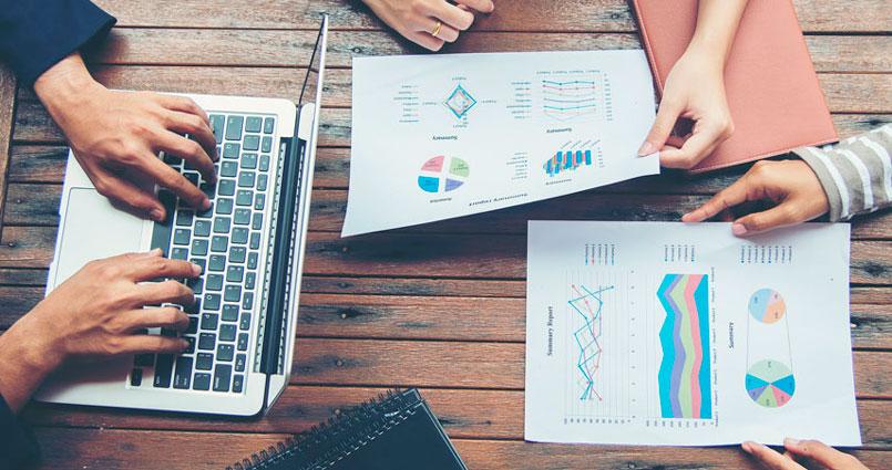 Pessoas avaliando relatórios e levantando dados como qualquer empresa com gestão de qualidade.
