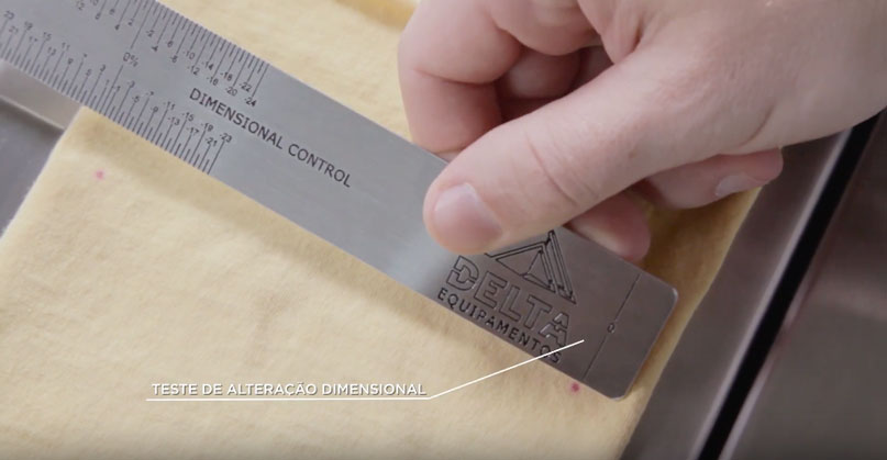 Técnico fazendo medição do teste dimensional em uma amostra de matéria-prima na indústria têxtil.