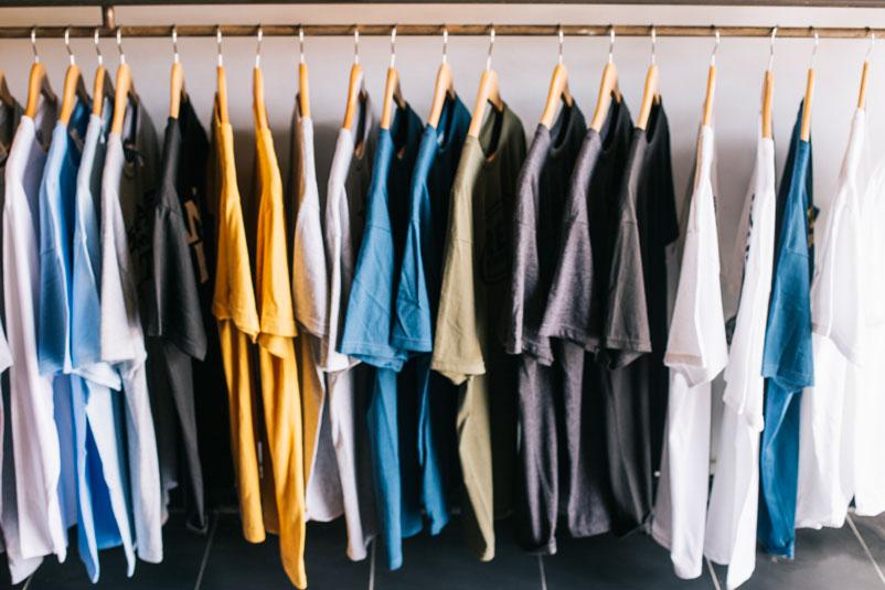 Camisetas recém produzidas com matéria-prima de alta qualidade penduradas em uma arará, são o resultado de uma modernização constante na indústria têxtil.